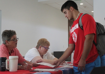 Voter registrars Paula Moore, left, and Susan Kabeschuh assist Luke Cerda, Vidor freshman, with voter registration during National Voter Registration Day in the Setzer Student Center, Tuesday. UP photo by Ricky Adams